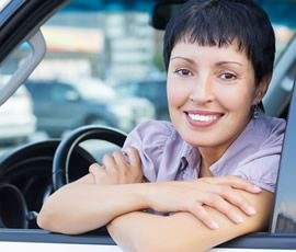 Female leaning out of car smiling
